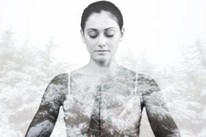 Peaceful woman in white sitting in lotus pose against snowy forest